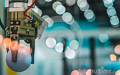 stock image of closeup robot hand machine picking up white ball on bokeh blurred background. use smart robot in manufacturing industry. robotic