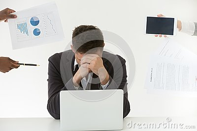 Depressed male employee tired by excessive workload and clients