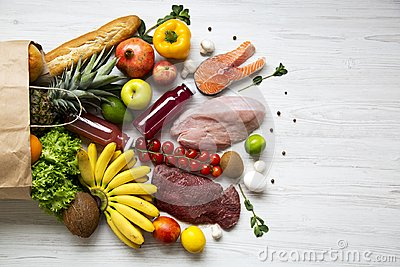 Full paper bag of healthy raw food on white wooden table. Cooking food background. Flat-lay of fresh fruits, veggies, greens, diff