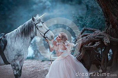 A fairy in a tender vintage dress hugs a unicorn. Fantastic magical, radiant horse. Background river and forest. Blonde
