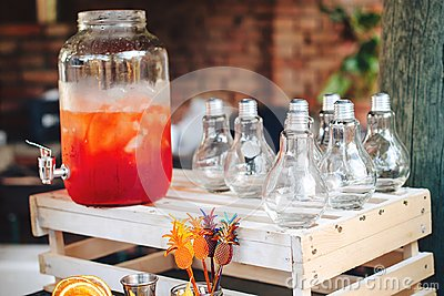 stock image of catering service. business, catering service. drinks on summer party. catering table with trendy glasses, big bottle of lemonade o