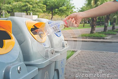 Woman hand putting used plastic bottle in public recycle bins or segregated waste bins in public park.
