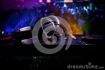 In selective focus of Pro dj controller.The DJ console deejay mixing desk at music party in nightclub with colored disco lights.
