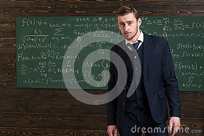 Talented mathematician. Man formal wear classic suit looks smart, chalkboard with equations background. Genius solved