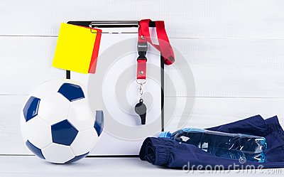 Soccer ball, a bottle of water on sports shorts, and a whistle, penalty cards and a tablet for recording a judge, backgr