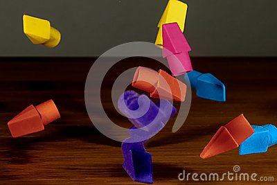 Pencil erasers caught in mid fall cascading onto a wooden deskt