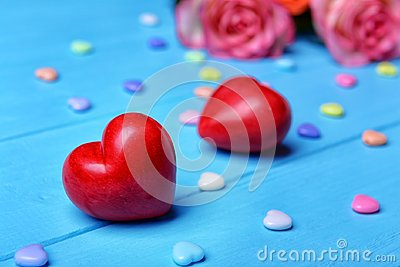 Red plastic hearts and roses on wooden background