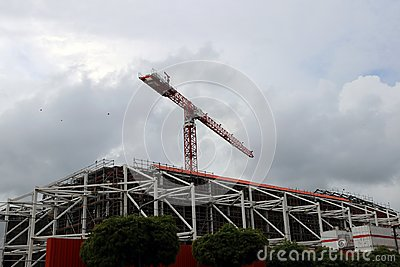 Big crane above the construction of building on cloud and sky background.