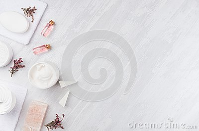 Handicraft natural cosmetics - white cream, soap, clay, rose oil, towel, pink flowers and bath accessories on soft light white.