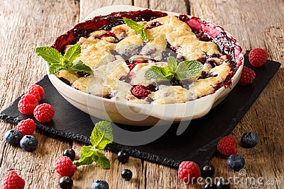 Summer berry cake with raspberry berries, currants and blueberries close-up in a baking dish. horizontal