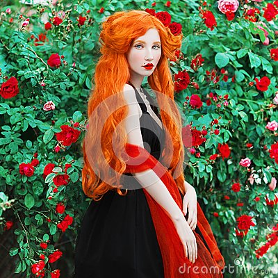 Young beautiful redhead queen with very long red hair. Fabulous renaissance woman in a black dress against the backdrop of beautif