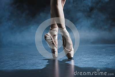 cropped view of ballet dancer in pointe shoes in dark studio