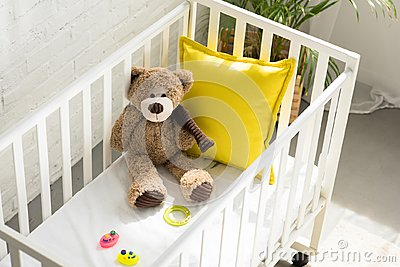 high angle view of teddy bear, other toys and yellow pillow in baby crib