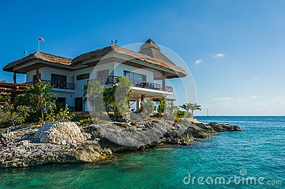 Thatched house on the rocks by the sea