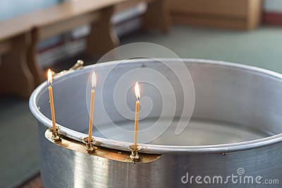 Big bowl of water for the baptism of a baby with wax candles. Orthodoxy. Greek Catholics
