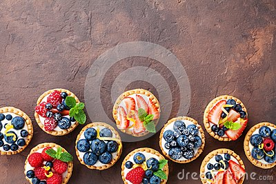 stock image of delicious berry tartlets or cake with cream cheese decorated lemon peel and mint leaf from above. tasty pastry desserts.