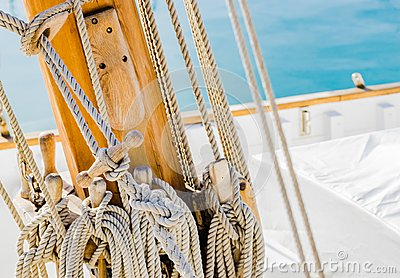 Yachting, rigging nautical ropes tied on wood mast on deck of classical sailing boat