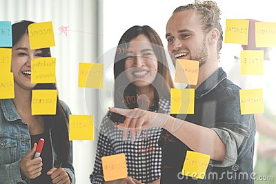 stock image of group of young successful creative multiethnic team smile and brainstorm on project together in modern office with post note or st