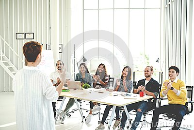 Businesswoman explain ideas to group of creative diverse team at modern office. Rear view of manager gesturing hand standing again