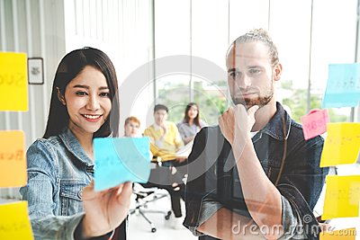 stock image of group of young successful creative multiethnic team smile and brainstorm on project together in modern office. woman sticking