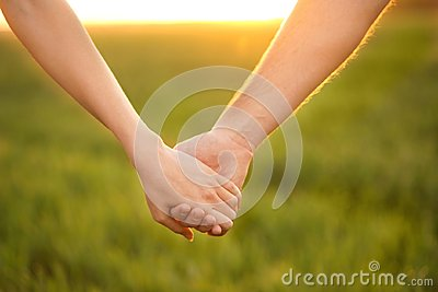 Young lovely couple holding hands in green field