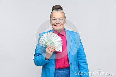 Happy adult woman holding many euro