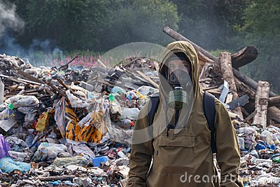 A working man in a gas mask against the backdrop of burning garbage. A lot of plastic bags thrown to the dump. From the plastic de