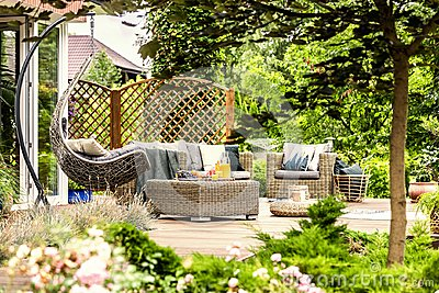Rattan garden furniture and hanging chair on wooden terrace of h
