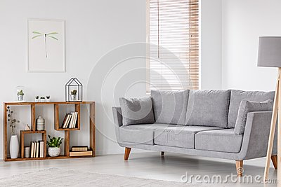 Real photo of a scandi living room interior with gray settee sta