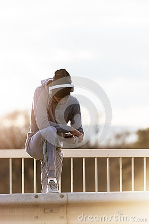 Handsome fit man taking a break after intensive training outdoors, texting on his smart phone wearing headphones