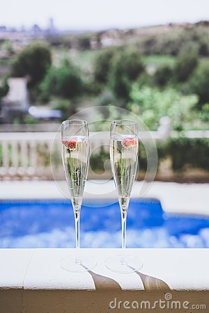 Two champagne glasses with strawberry on sunny terrace outdoor patio overlooking swimming pool at summer day outside of