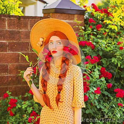 Breathtaking valentines day background. Retro girl with red lips in stylish yellow dress in dots in beautiful summer roses garden.