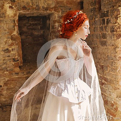 Young renaissance redhead princess with hairstyle in the old castle. Fabulous rococo queen in white dress against the backdrop of