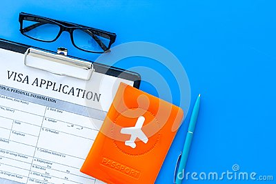 Documents for travel abroad. Visa application form, pen, passport cover with airplane silhouette on blue background top