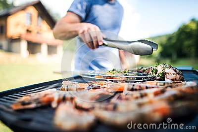 Unrecognizable man cooking seafood on a barbecue grill in the backyard.