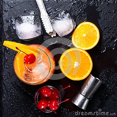 Tequila Sunrise cocktail, orange, ice cubes, maraschino cherries, ice tongs and jigger on a wet black slate tray. Cocktail Set. To