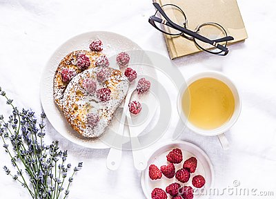 Brioche french toast with raspberry, powdered sugar and green tea. Cozy home still life, free time rest. On a light background, to