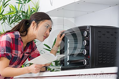 Lady looking at countertop oven holding instructions