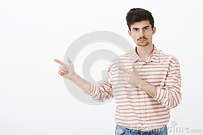 Indoor portrait of serious jealous boyfriend with beard and moustache, pointing left with finger gun gestures and