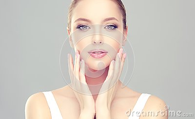 Alluring woman with clean fresh skin is touching the face tenderly.
