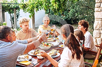 Big family have a dinner on garden terrace