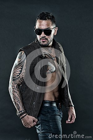 Tattooed man with six pack and ab. Bearded man with tattoo on chest and arms. Tattoo model with beard on unshaven face
