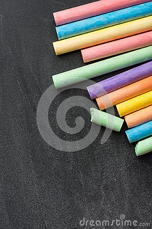 stock image of row pile of multicolored chalks crayons on dark scratched blackboard. back to school business creativity graphic design