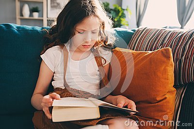 Concentrated kid girl reading interesting book at home