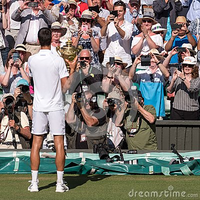 Novac Djokovic, Serbian player, wins Wimbledon. In the photo he holds the trophy on centre court in front of press photographers.