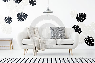 Patterned pillow and blanket on sofa in white living room interior with monstera leaves. Real photo