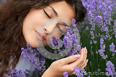 Beautiful young woman portrait on lavender flowers background, face closeup