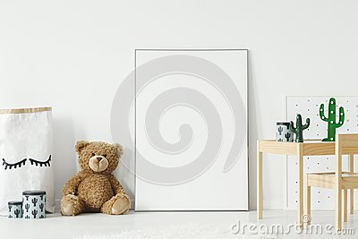 Mockup poster, teddy bear and material basket placed on the floor in white room interior with wooden table and small chair. Paste