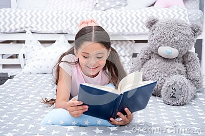 Read fairytale in bed. Girl child lay bed with teddy bear read book. Kid prepare to go to bed. Time for evening