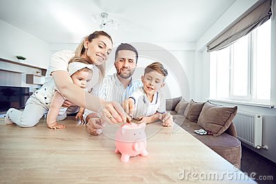 A smiling family saves money with a piggy bank.